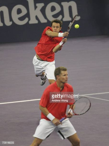 Daniel Nestor of Canada returns a serve as doubles partner Mark Knowles of Bahamas looks on during their match against Fabrice Santoro of France and...