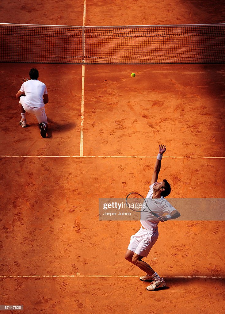 Daniel Nestor (R) of Canada serves the ball flanked by his doubles partner Nenad Zimonjic of Serbia to Simon Aspelin of Sweden and Wesley Moodie of South Africa during the doubles final of the Madrid Open tennis tournament at the Caja Magica on May 17, 2009 in Madrid, Spain. Nestor and Zimonjic won their final match in straight sets.