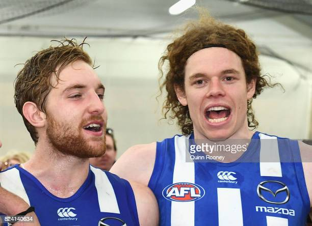 Daniel Nielson and Ben Brown of the Kangaroos sing the song in the rooms after winning the round 19 AFL match between the North Melbourne Kangaroos...