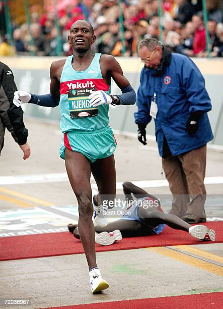Daniel Njenga of Kenya runs by Robert Cheruiyot of Kenya who collpased after his first place finish in The LaSalle Bank Chicago Marathon October 22...
