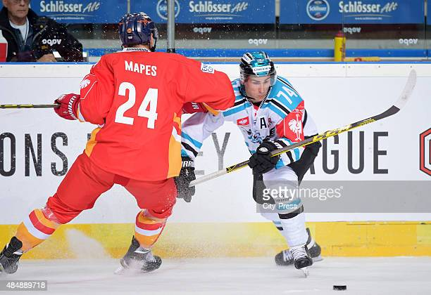 Daniel Oberkofler of the Black Wings Linz passes the puck against Corey Mapses of the Duesseldorfer EG during the game between Duesseldorfer EG and...