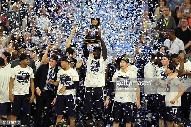 Daniel Ochefu of the Villanova Wildcats hoists the trophy after the Villanova Wildcats defeat the North Carolina Tar Heels 7774 to win the 2016 NCAA...
