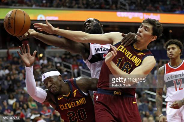 Daniel Ochefu of the Washington Wizards battles Cedi Osman of the Cleveland Cavaliers for a rebound in the second half during a preseason game at...