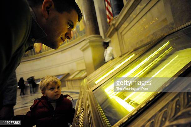 Daniel Omer and his son Adam Omer of Hampton Roads VA gaze at the Constitution of the United States on January 6 2011 at the National Archives in...