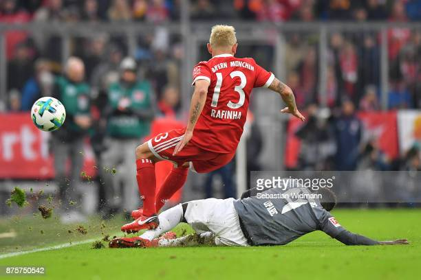 Daniel Opare of Augsburg foules Rafinha of Bayern Muenchen during the Bundesliga match between FC Bayern Muenchen and FC Augsburg at Allianz Arena on...