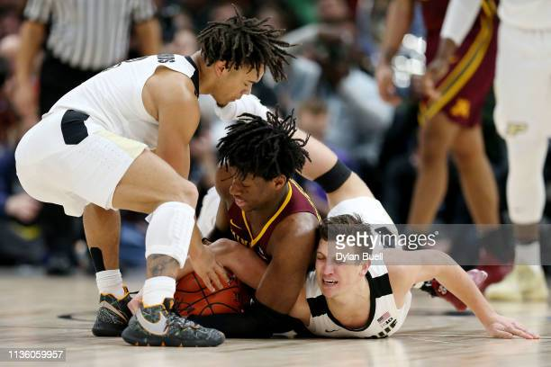 Daniel Oturu of the Minnesota Golden Gophers battles for a loose ball against Carsen Edwards and Grady Eifert of the Purdue Boilermakers in the first...