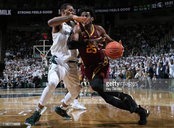 Daniel Oturu of the Minnesota Golden Gophers drives to the basket while defended by Xavier Tillman of the Michigan State Spartans in the second half...