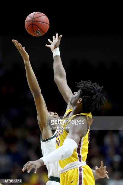 Daniel Oturu of the Minnesota Golden Gophers tips off the ball against the Michigan State Spartans during the first half in the second round game of...