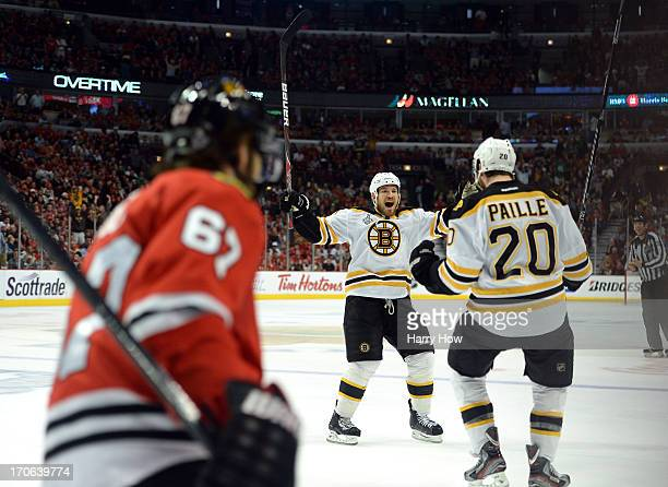 Daniel Paille and Andrew Ference of the Boston Bruins celebrate after Paille scored the gamewinning goal in the first overtime against Michael Frolik...