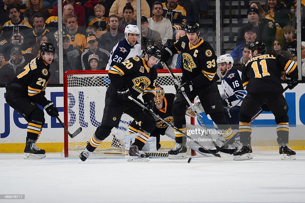 Daniel Paille #20 and Zdeno Chara #33 of the Boston Bruins fight for the puck against the Winnipeg Jets at the TD Garden on January 4, 2014 in Boston, Massachusetts.