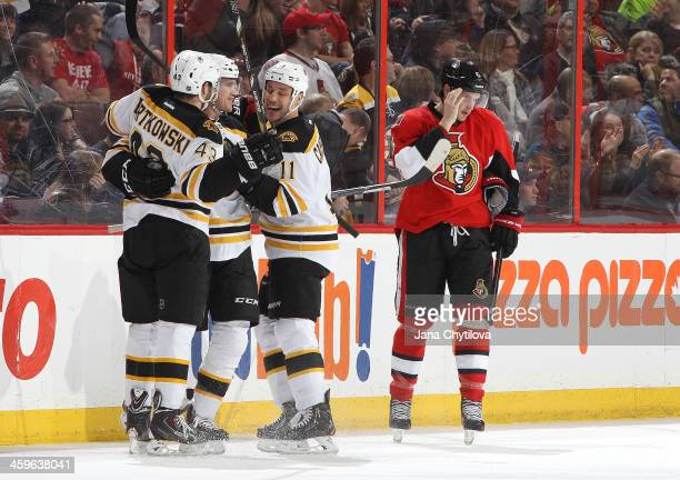 Daniel Paille of the Boston Bruins celebrates his firstperiod goal with teammates Matt Bartkowski and Gregory Campbell as Bobby Ryan of the Ottawa...