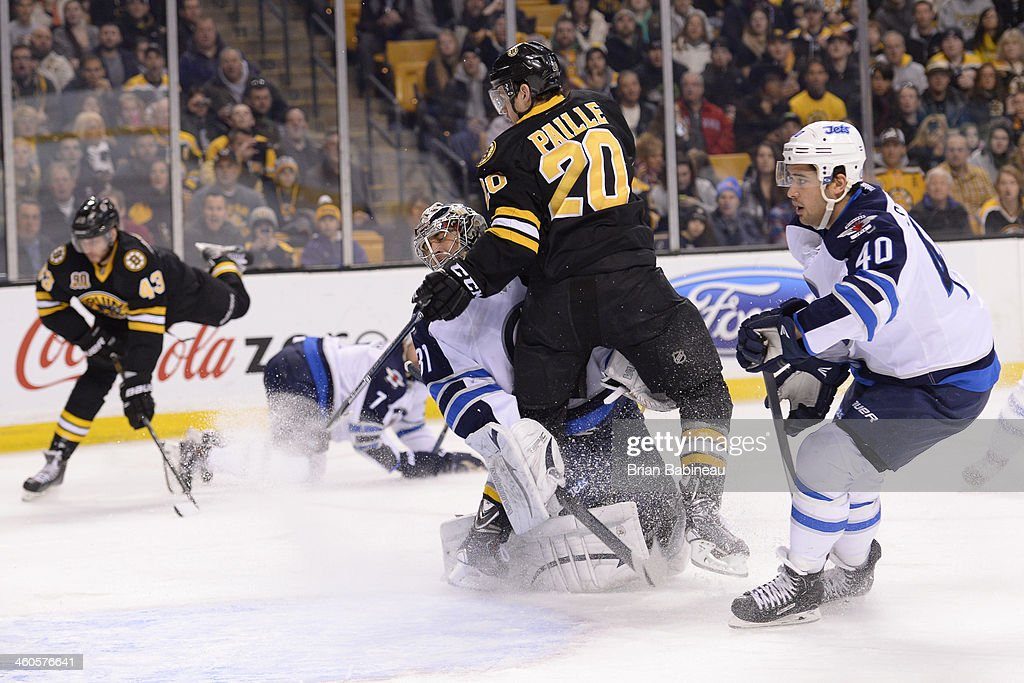 Daniel Paille #20 of the Boston Bruins collides with Ondrej Pavelec #31 of the Winnipeg Jets at the TD Garden on January 4, 2014 in Boston, Massachusetts.