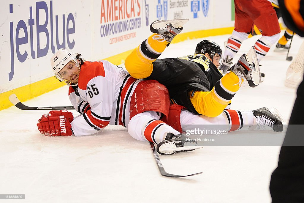 Daniel Paille #20 of the Boston Bruins falls on top of Ron Hainsey #65 of the Carolina Hurricanes at the TD Garden on November 23, 2013 in Boston, Massachusetts.