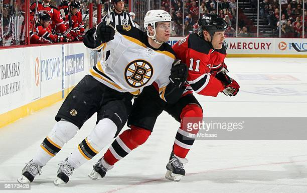 Daniel Paille of the Boston Bruins skates against Dean McAmmond of the New Jersey Devils at the Prudential Center on March 30 2010 in Newark New...