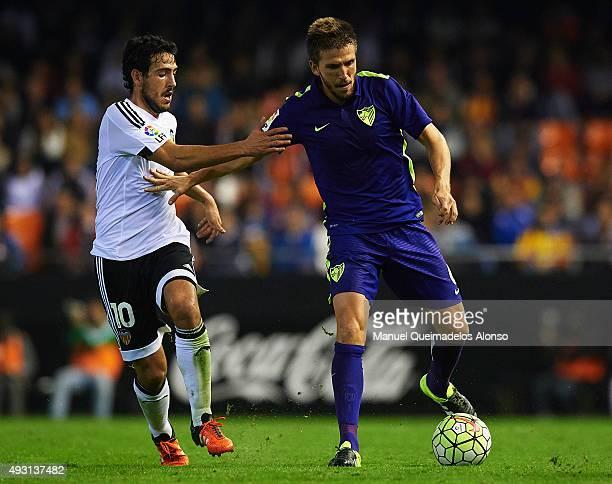 Daniel Parejo of Valencia competes for the ball with Ignacio Camacho of Malaga during the La Liga match between Valencia CF and Malaga CF at Estadi...