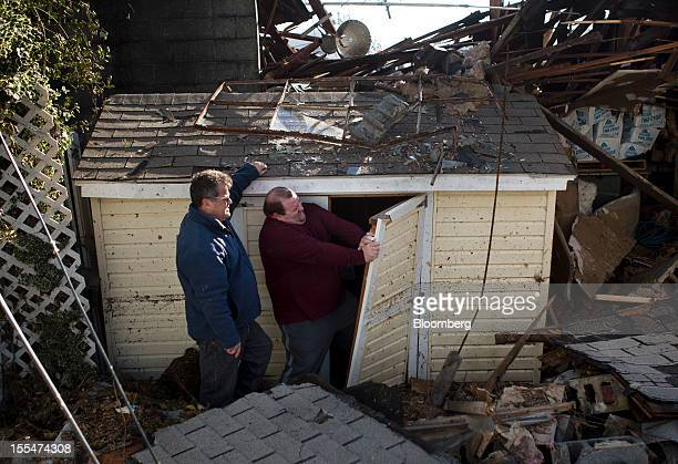 Daniel Parker right tries to get into a shed damaged during Hurricane Sandy outside his home as his father John Parker looks on in the Paradise Park...