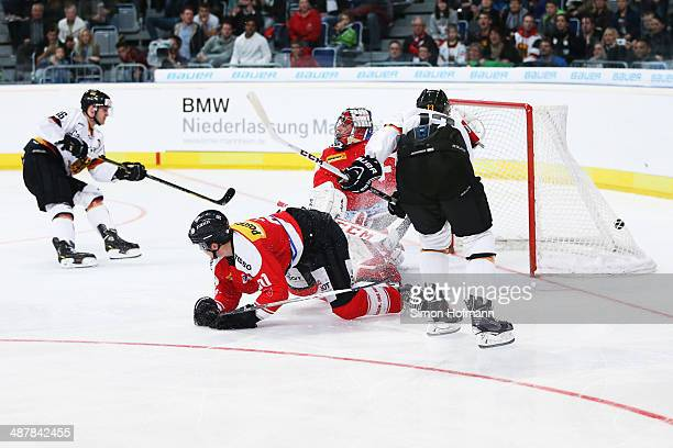 Daniel Pietta of Germany scores his team's first goal against goalkeeper Robert Mayer of Switzerland during the International Icehockey Friendly...
