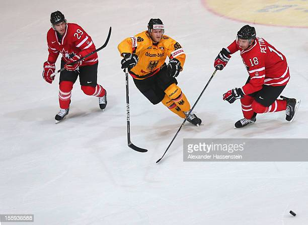 Daniel Pietta of Germany skate with Matt Pettinger of Canada and his team mate Stephen Dixon during the German Ice Hockey Cup 2012 first round match...