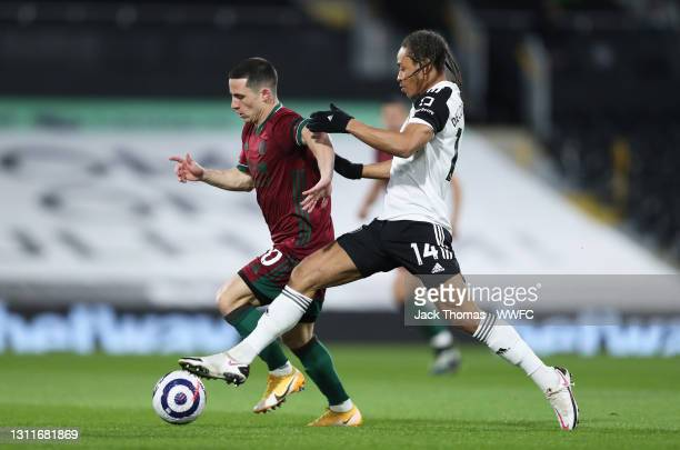 Daniel Podence of Wolverhampton Wanderers battles for possession with Bobby De Cordova-Reid of Fulham during the Premier League match between Fulham...
