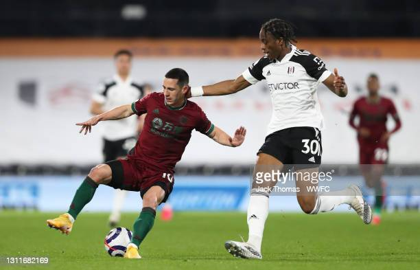 Daniel Podence of Wolverhampton Wanderers battles for possession with Terence Kongolo of Fulham during the Premier League match between Fulham and...