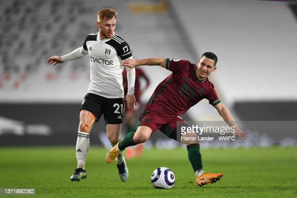 Daniel Podence of Wolverhampton Wanderers battles for possession with Harrison Reed of Fulham during the Premier League match between Fulham and...