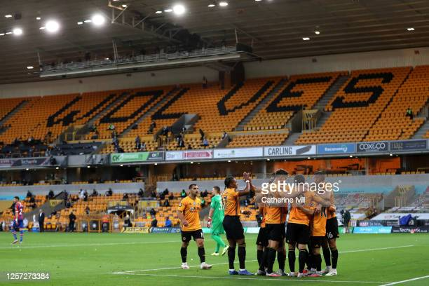 Daniel Podence of Wolverhampton Wanderers celebrates with teammates in front of empty stands after scoring his team's first goal during the Premier...