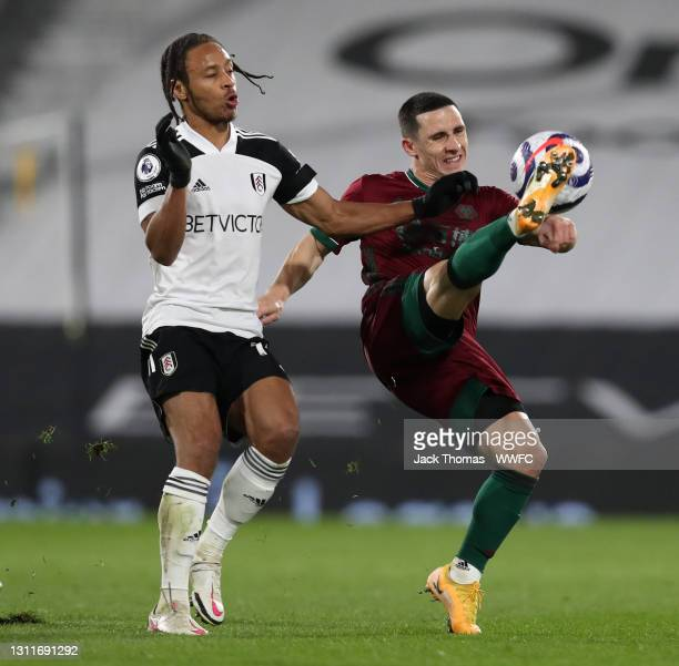Daniel Podence of Wolverhampton Wanderers clears the ball under pressure from Bobby De Cordova-Reid of Fulham during the Premier League match between...