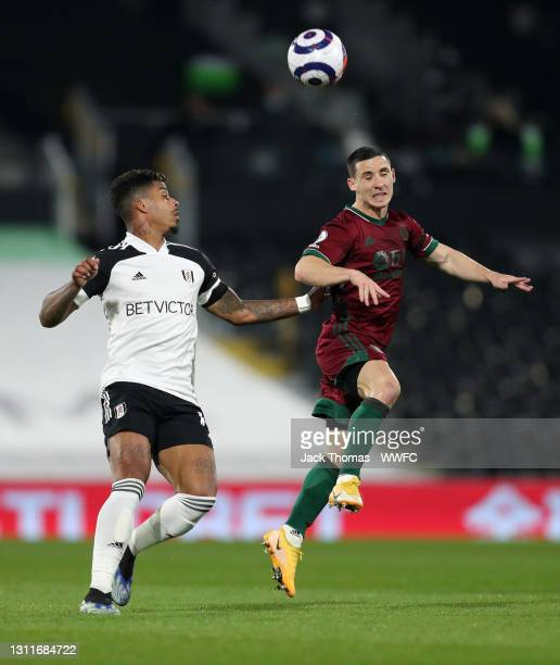Daniel Podence of Wolverhampton Wanderers heads the ball under pressure from Mario Lemina of Fulham during the Premier League match between Fulham...