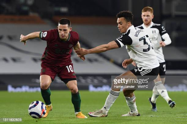 Daniel Podence of Wolverhampton Wanderers is challenged by Antonee Robinson of Fulham during the Premier League match between Fulham and...