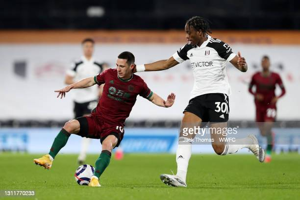 Daniel Podence of Wolverhampton Wanderers is challenged by Terence Kongolo of Fulham during the Premier League match between Fulham and Wolverhampton...