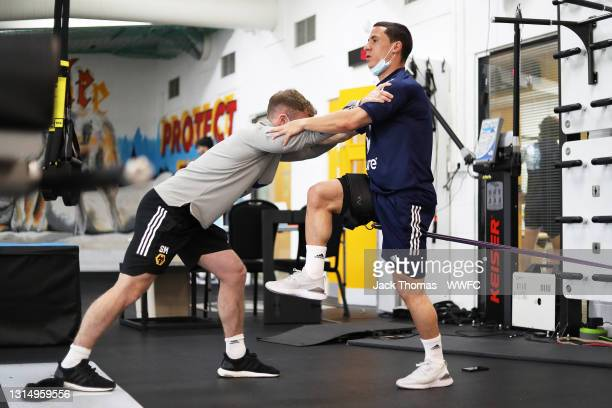 Daniel Podence of Wolverhampton Wanderers stretches with Sean Miller, Strength and Conditioning Coach of Wolverhampton Wanderers in the gym during a...