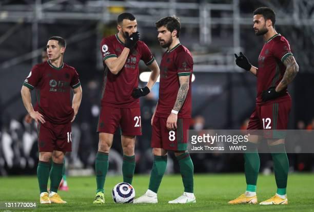 Daniel Podence, Romain Saiss, Ruben Neves and Willian Jose of Wolverhampton Wanderers prepare to take a free kick during the Premier League match...
