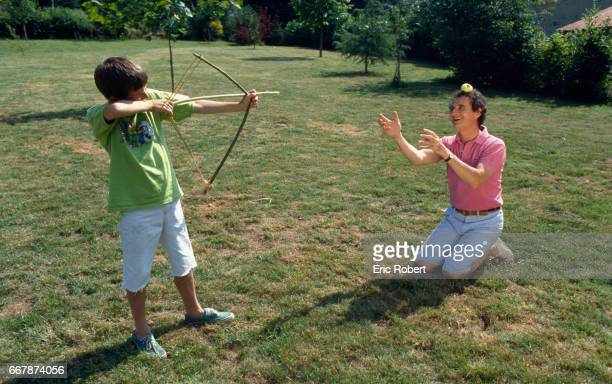 Daniel Prevost kneels with an apple on his head while his son Erling takes aim with a bow