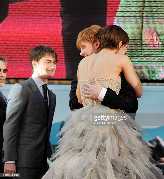 Daniel Radcliffe looks on as Rupert Grint and Emma Watson embrace at the World Premiere of 'Harry Potter And The Deathly Hallows Part 2' in Trafalgar...
