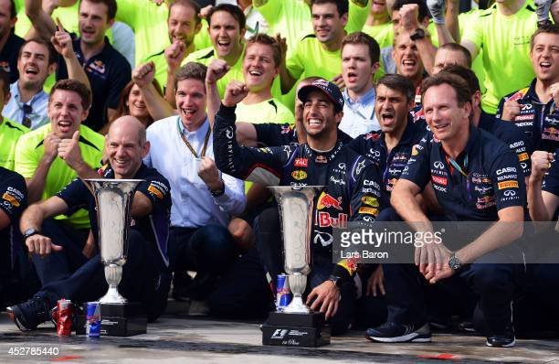 Daniel Ricciardo of Australia and Infiniti Red Bull Racing celebrates victory with the trophy and members of his team including Infiniti Red Bull...