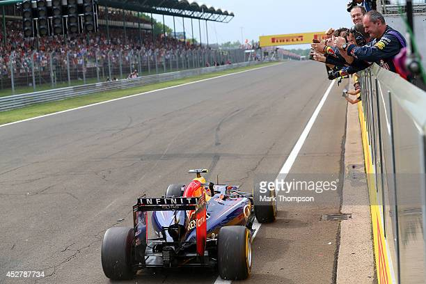 Daniel Ricciardo of Australia and Infiniti Red Bull Racing drives past members of his team on the pit straight as they applaud him during the...
