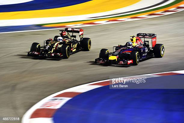 Daniel Ricciardo of Australia and Infiniti Red Bull Racing drives next to Romain Grosjean of France and Lotus during practice ahead of the Singapore...