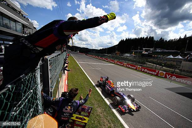 Daniel Ricciardo of Australia and Infiniti Red Bull Racing is cheered on by members of his team after crossing the finish line to win the Belgian...