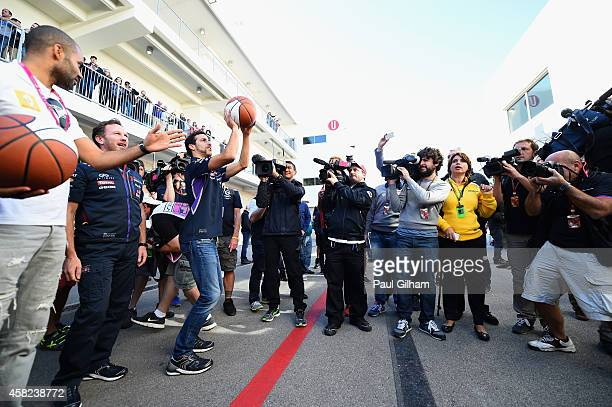 Daniel Ricciardo of Australia and Infiniti Red Bull Racing shoots hoops with Tony Parker after qualifying for the United States Formula One Grand...