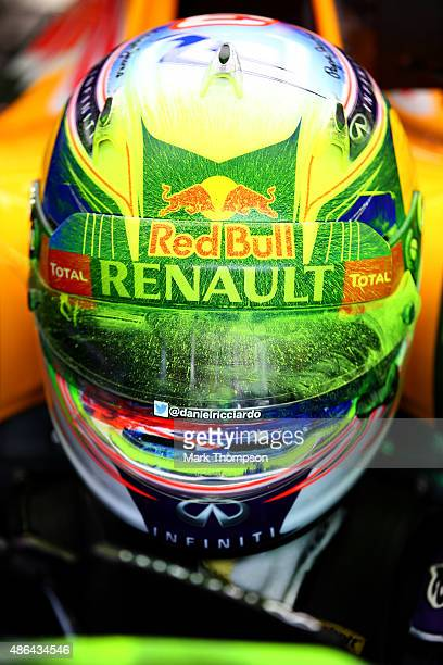Daniel Ricciardo of Australia and Infiniti Red Bull Racing sits in his car after returning to the garage with his helmet covered in flowvis paint...