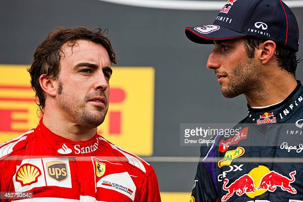 Daniel Ricciardo of Australia and Infiniti Red Bull Racing speaks with Fernando Alonso of Spain and Ferrari as he celebrates victory on the podium...