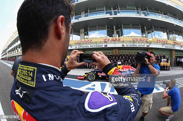 Daniel Ricciardo of Australia and Infiniti Red Bull Racing takes a photograph on his phone before the team photograph in the pit lane before the Abu...