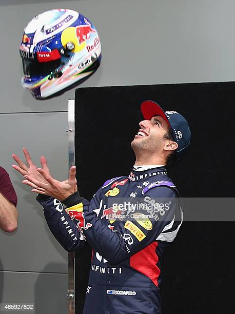 Daniel Ricciardo of Australia and Infiniti Red Bull Racing tosses his helmet in the air as he poses for photographers during previews to the...