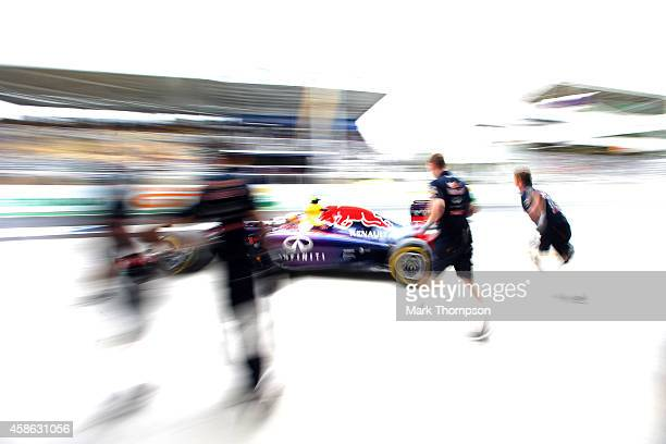 Daniel Ricciardo of Australia and Infiniti Red Bull Racing's team run out as he returns to the garage during qualifying for the Brazilian Formula One...