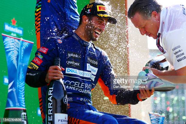 Daniel Ricciardo of Australia and McLaren celebrates with a shoey on the podium as McLaren CEO Zak Brown pours the sparkling wine following his...