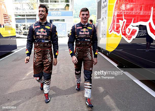 Daniel Ricciardo of Australia and Red Bull Racing and Max Verstappen of Netherlands and Red Bull Racing walk to the garage in lederhosen themed...