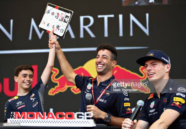 Daniel Ricciardo of Australia and Red Bull Racing and Max Verstappen of Netherlands and Red Bull Racing with a competition winner on the fanzone...