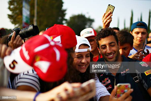 Daniel Ricciardo of Australia and Red Bull Racing arrives at the circuit and poses for a photo with fans during final practice for the Formula One...