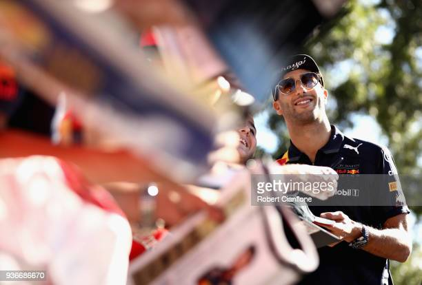 Daniel Ricciardo of Australia and Red Bull Racing arrives at the circuit and poses for a photo with fans before practice for the Australian Formula...