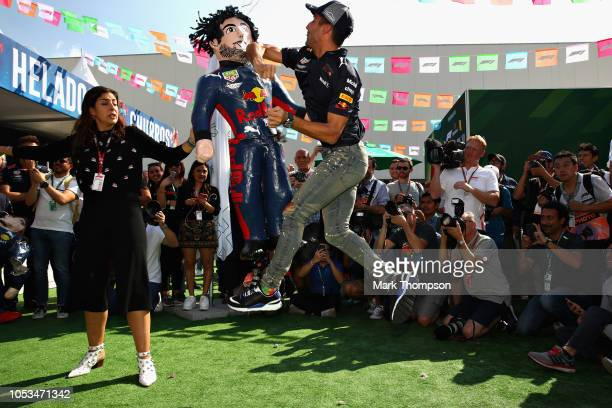 Daniel Ricciardo of Australia and Red Bull Racing attempts to smash a pinata in the Paddock during previews ahead of the Formula One Grand Prix of...